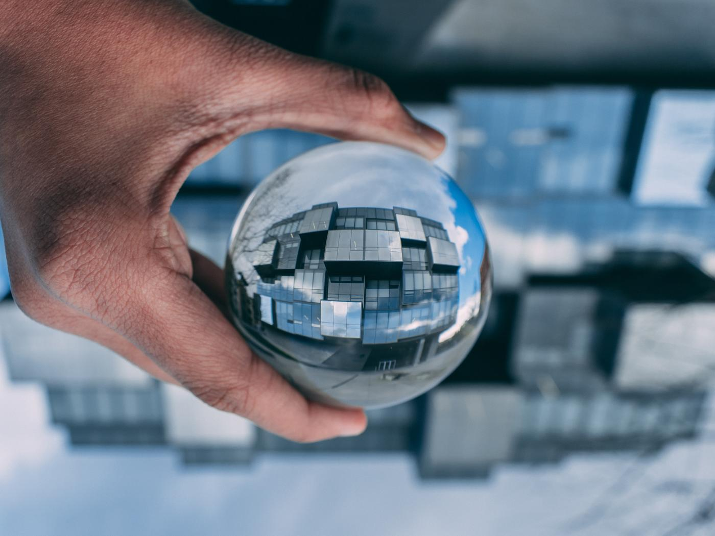 lensball perspective building holding hand