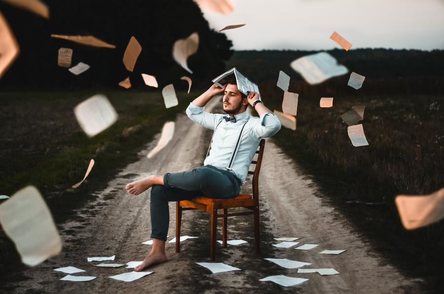 Man sitting on dirt road with paper flying around him