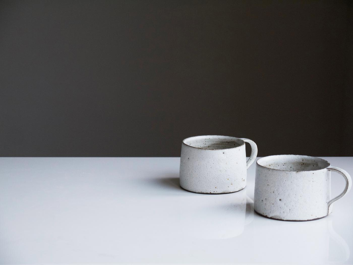 two mugs sitting on a counter surface